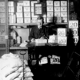 US Treasury Department official, surrounded by packages of newly printed currency, counting and wrapping dollar bills by National Archives and Records Administration
