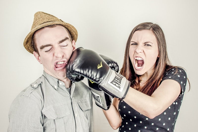 woman with boxing glove punching man in the face